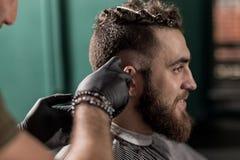 El hombre hermoso brutal con la barba se sienta en una peluquería de caballeros El peluquero afeita los pelos en el lado foto de archivo