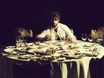 El hombre hermoso come en la tabla imágenes de archivo libres de regalías