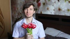 El hombre hermoso con el afecto presenta las flores a la cámara - los tulipanes almacen de metraje de vídeo
