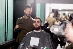 El hombre hermoso con la barba sienta en una peluquería de caballeros en frente el espejo El peluquero hace un ajuste del pelo fotos de archivo