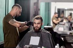 El hombre hermoso con la barba sienta en una peluquería de caballeros en frente el espejo El peluquero hace un ajuste del pelo imagen de archivo libre de regalías