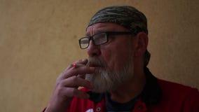 El hombre hermoso con una barba gris y los vidrios fuma un cigarrillo y miradas en la distancia cuidadosamente Su venda almacen de video