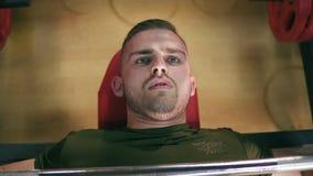 El hombre hermoso concentrado con los ojos azules que ejercita su pecho muscles mientras que banco que clava el gimnasio Tirado e almacen de metraje de vídeo