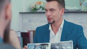 El hombre hermoso elegante en una chaqueta muestra a clientes un folleto almacen de metraje de vídeo