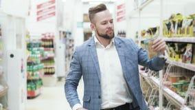 El hombre hermoso en chaqueta elige las especias en un supermercado almacen de video