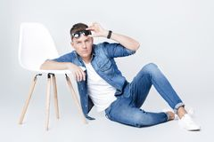 El hombre hermoso en dril de algodón se sienta en silla Fotografía de archivo