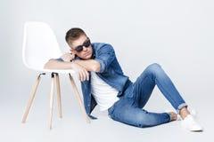 El hombre hermoso en dril de algodón se sienta en silla Imagen de archivo libre de regalías