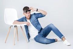 El hombre hermoso en dril de algodón se sienta en silla Fotografía de archivo libre de regalías