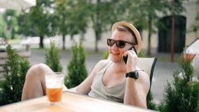 El hombre hermoso en gafas de sol con el sombrero está hablando en el teléfono, sonriendo Él es bebidas al cóctel y se relaja almacen de metraje de vídeo