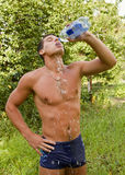 El hombre hermoso en un bañador con un agua b Fotografía de archivo libre de regalías