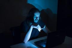 El hombre hermoso es cigarrillos del nido de abeja delante de su ordenador Foto de archivo libre de regalías