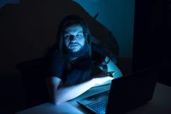 El hombre hermoso es cigarrillos del nido de abeja delante de su ordenador Imagenes de archivo