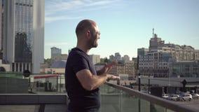 El hombre hermoso es derribo feliz en el balcón urbano
