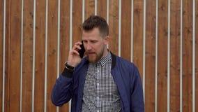 El hombre hermoso está hablando por el teléfono móvil emocionalmente, colocándose al aire libre almacen de video