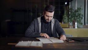 El hombre hermoso está leyendo el menú que se sienta en un restaurante en rotura de cena y que llama a un camarero almacen de metraje de vídeo