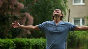 El hombre hermoso feliz joven goza de la lluvia del verano que se coloca en parque verde y aumenta sus manos para arriba almacen de video