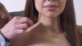 El hombre hermoso feliz puso el cuello hermoso de la mujer del aruond del collar