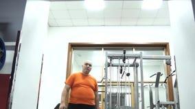 El hombre hermoso gordo en camiseta anaranjada en un gimnasio está saliendo