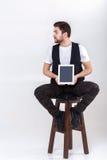 El hombre hermoso joven con la barba en la camisa blanca y la tenencia negra del chaleco hacen tabletas y se sientan en silla en  Foto de archivo