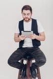 El hombre hermoso joven con la barba en la camisa blanca y la tenencia negra del chaleco hacen tabletas y se sientan en silla en  Imágenes de archivo libres de regalías