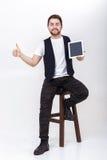 El hombre hermoso joven con la barba en la camisa blanca y tableta negra de la tenencia del chaleco y la demostración manosean co Fotografía de archivo
