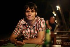 El hombre hermoso joven con la cerveza de consumición del smartphone en la barra de la playa que se sienta por el mar en la noche Imágenes de archivo libres de regalías