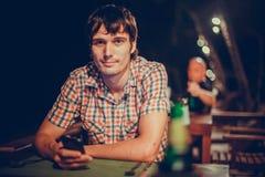 El hombre hermoso joven con la cerveza de consumición del smartphone en la barra de la playa que se sienta por el mar en la noche Foto de archivo