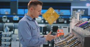 El hombre hermoso joven en camisa azul elige un nuevo teléfono móvil en una tienda de la electrónica Compra moderna de la tecnolo almacen de video