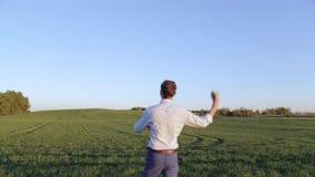 El hombre hermoso joven en camisa azul está poniendo en marcha el avión de papel en campo verde en puesta del sol almacen de video