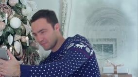 El hombre hermoso joven en una Navidad hizo punto el suéter que tomaba selfies en una tableta almacen de metraje de vídeo