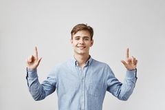 El hombre hermoso joven está mirando para arriba, señalando sus fingeres esperando que todos los números en su boleto de lotería  imágenes de archivo libres de regalías