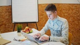 El hombre hermoso joven está trabajando en el ordenador portátil en un cuarto acogedor de la oficina almacen de metraje de vídeo
