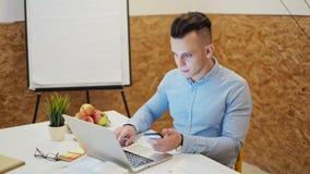 El hombre hermoso joven está trabajando en el ordenador portátil en un cuarto acogedor de la oficina usando Smartphone metrajes