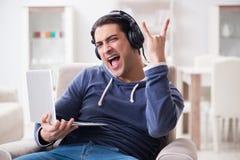 El hombre hermoso joven que escucha la música con los auriculares Imagen de archivo libre de regalías