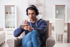 El hombre hermoso joven que escucha la música con los auriculares Imagen de archivo