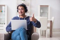 El hombre hermoso joven que escucha la música con los auriculares Fotografía de archivo