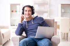 El hombre hermoso joven que escucha la música con los auriculares Foto de archivo libre de regalías
