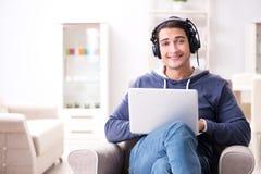 El hombre hermoso joven que escucha la música con los auriculares Imagenes de archivo