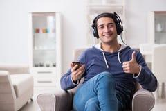 El hombre hermoso joven que escucha la música con los auriculares Imágenes de archivo libres de regalías
