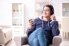 El hombre hermoso joven que escucha la música con los auriculares Fotos de archivo