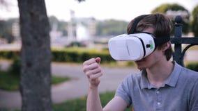 El hombre hermoso joven que lleva gafas de la realidad virtual en una ciudad parquea almacen de metraje de vídeo