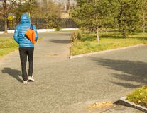 El hombre hermoso joven que lleva una chaqueta azul con los deportes empaqueta, caminando en parque, vista posterior Fotos de archivo libres de regalías