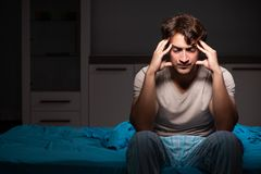 El hombre hermoso joven que sufre de insomnio en cama foto de archivo libre de regalías