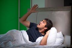 El hombre hermoso joven que sufre de insomnio en casa imagenes de archivo
