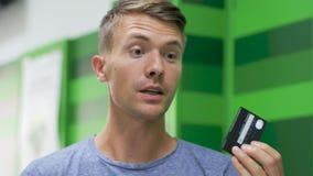 El hombre hermoso joven visita el banco almacen de metraje de vídeo
