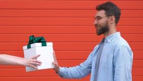El hombre hermoso muestra que muestra de la parada con una expresión seria y confiada de la cara no aceptó como caja de regalo metrajes