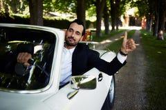 El hombre hermoso onfident del ¡de Ð se sienta en su nuevo coche convertible que hace gesto estupendo con el finger Fotos de archivo