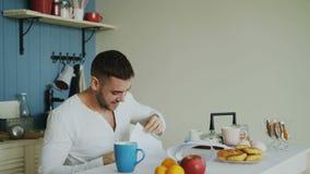 El hombre hermoso recibe la letra de la lectura de las buenas noticias en la cocina mientras que tenga madrugada del desayuno en  almacen de metraje de vídeo