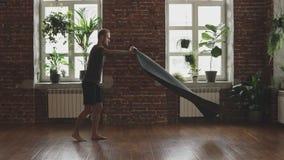 El hombre hermoso se prepara para hacer práctica de la yoga de la mañana Estera negra masculina de la yoga que se considera almacen de video