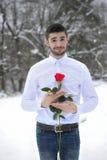 El hombre hermoso se vistió en una camisa blanca y sostener una rosa Imágenes de archivo libres de regalías